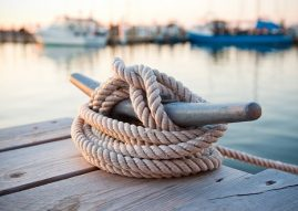 Nautical boating knot tied around a dock post with multiple boats docked in the water blurred in the background/